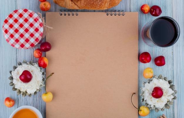 灰色の背景に配置されたジュースの新鮮な熟した黄色と赤のチェリーグラスとスケッチブックとカッテージチーズのトップビュー