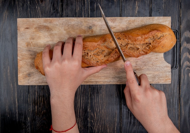 木製の背景にまな板の上のナイフで黒いバゲットを切る手のトップビュー
