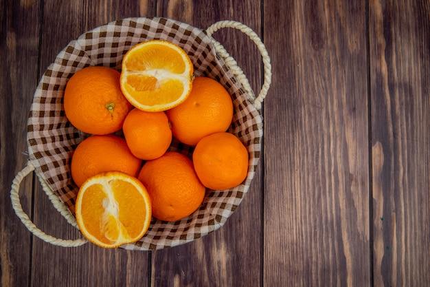 コピースペースを持つ素朴な木製の表面の枝編み細工品バスケットで新鮮な熟したオレンジのトップビュー