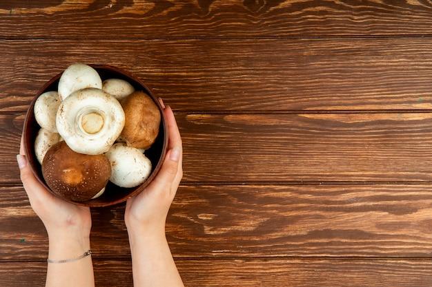 コピースペースを持つ素朴な背景に木製のボウルに新鮮なキノコを保持している女性の手の上から見る