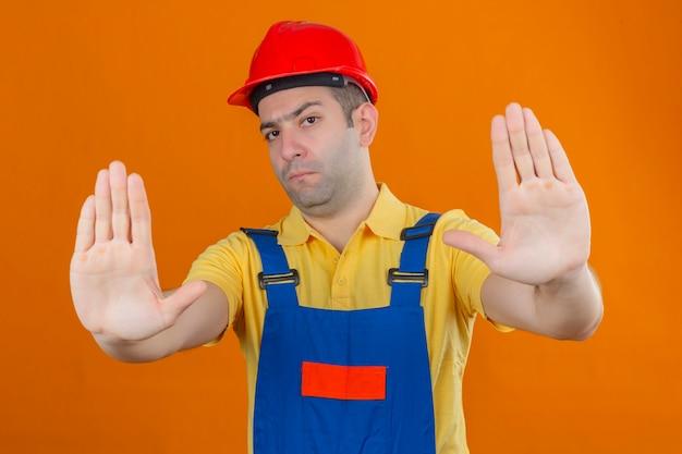 オレンジに分離された一時停止の標識を作る深刻な顔をした制服と赤い安全ヘルメットの建設労働者