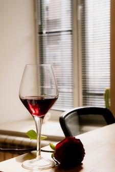 ウィンドウの背景に木製のテーブルの赤ワインのガラスの近くに横たわって赤い色ローズの側面図