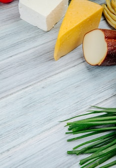 Вид сбоку различных видов сыра с зеленым луком на сером деревянном столе с копией пространства