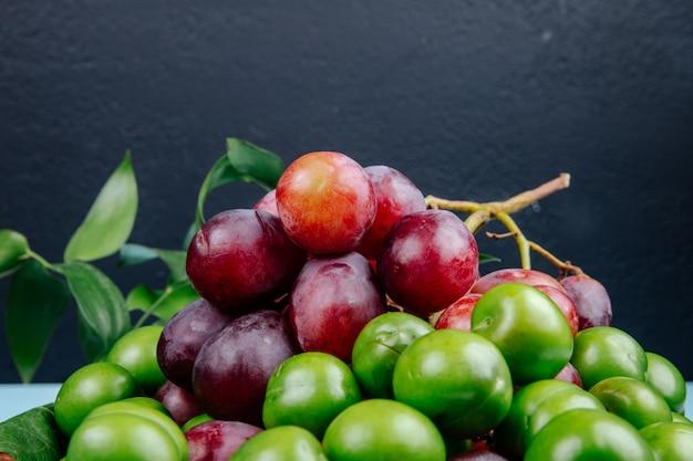Вид сбоку свежего сладкого винограда с зелеными кислыми сливами в плетеной корзине на черном столе