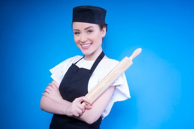 Милая шеф-повар скрестила руки и держит в руке скалку
