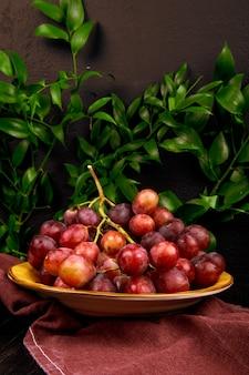 Вид сверху кучу свежего сладкого винограда в тарелку на зеленом столе