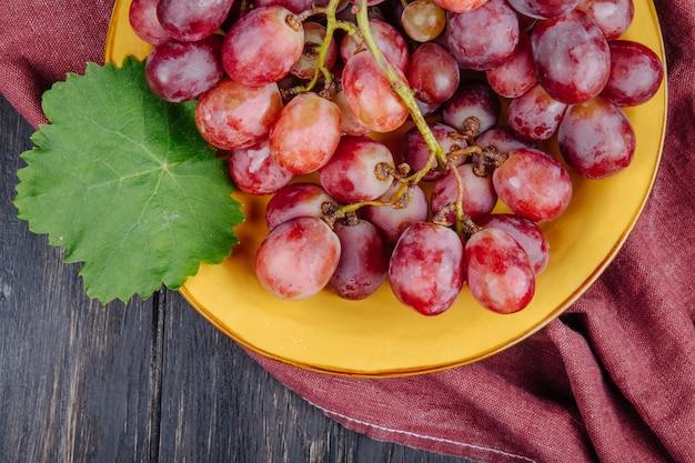 Вид сверху кучу свежего сладкого винограда в тарелку с зелеными листьями на деревенском столе
