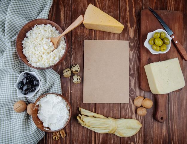 木製の素朴なテーブルに格子縞の生地に茶色の紙のシートと木製のボウルにカッテージチーズとピクルスオリーブ、ウズラの卵、クルミとさまざまなチーズの部分の平面図