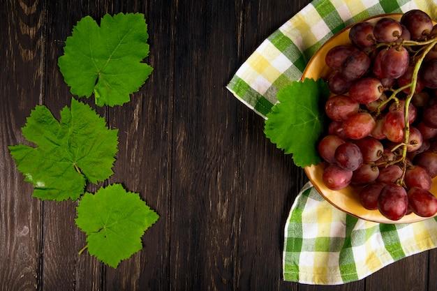 Вид сверху свежего сладкого винограда в тарелку с зелеными листьями винограда на темный деревянный стол с копией пространства