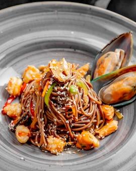 Лапша с морепродуктами, перцем, кунжутом и соусом