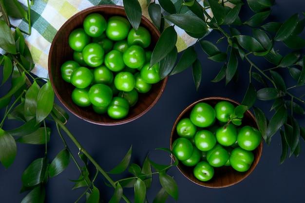Вид сверху кислые зеленые сливы в деревянные чаши и листья рускуса на черном столе
