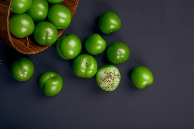 Вид сверху кислых зеленых слив, разбросанных из деревянной миски на черном столе