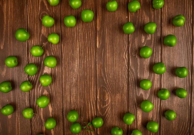Взгляд сверху кислых зеленых слив разбросанных на деревянный стол с космосом экземпляра
