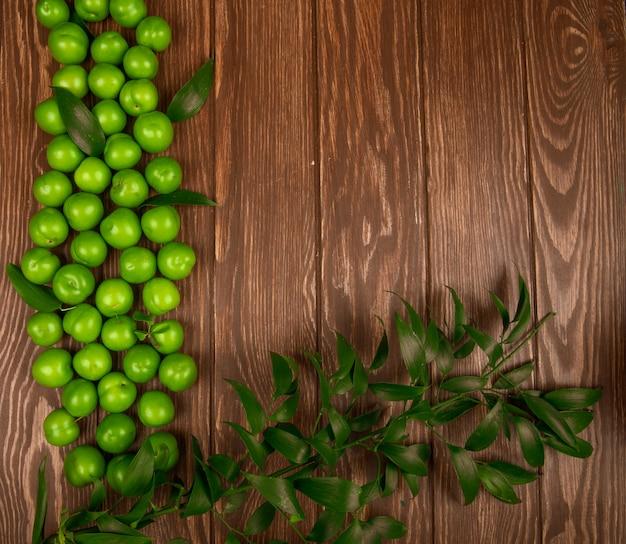 Вид сверху кислые зеленые сливы с руском листья на деревянный стол с копией пространства