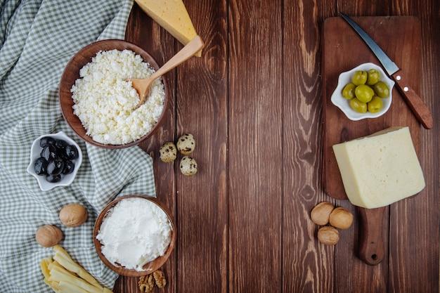Вид сверху различных сыров и творога в миску с грецкими орехами, перепелиными яйцами и маринованными оливками на деревянной разделочной доске с ножом на деревенском столе