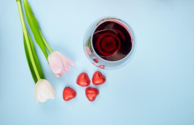 青いテーブルに散らばったハート型のキャンディと赤いホイルとワインのグラスと白とピンクの色のチューリップの花の上から見る