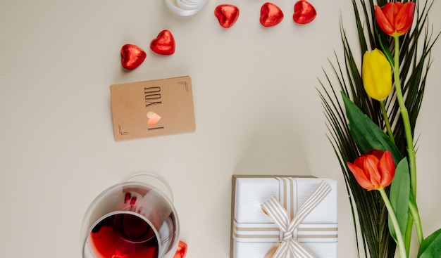 白いテーブルに赤い箔、ワインのガラス、小さな茶色の紙のグリーティングカード、ギフトボックスに包まれたハート型のチョコレート菓子とチューリップの花束のトップビュー