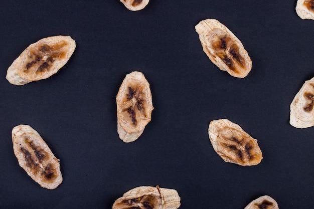 黒の背景に分離された乾燥バナナチップのトップビュー