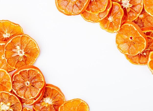 コピースペースと白い背景の上に配置された乾燥したオレンジスライスのトップビュー
