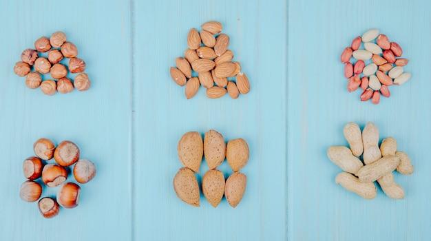 Взгляд сверху смешанного кучи гаек изолированных на голубой предпосылке фундуки и арахисах миндалин