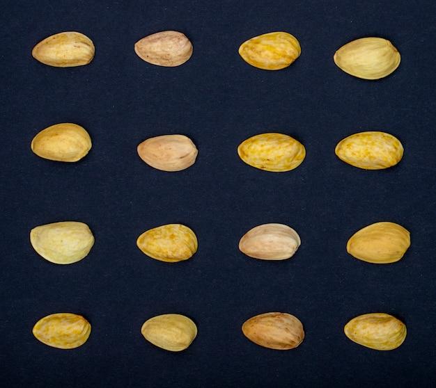 Вид сверху фисташковых орехов, изолированных на черном фоне