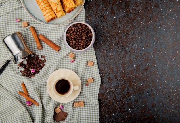 Вид сверху на чашку кофе и кофейных зерен в миску с палочки корицы на клетчатой скатертью с копией пространства