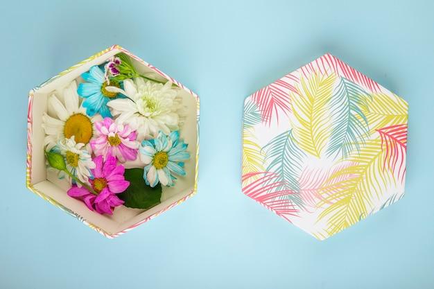 Вид сверху подарочной коробке, наполненной разноцветными цветами хризантемы с ромашкой на синем фоне