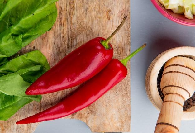 Взгляд конца-вверх овощей как красные перцы и шпинат на разделочной доске с семенами черного перца в дробилке чеснока на голубой предпосылке