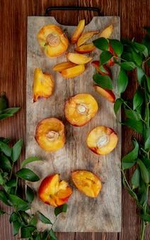 素朴なテーブルに緑の葉と木製のまな板に新鮮な熟した桃の半分のトップビュー