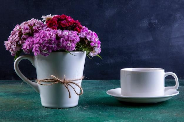Вид спереди разноцветных цветов в белой чашке с чашкой чая на блюдце