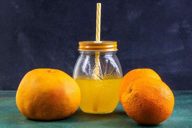 Вид спереди апельсинов с апельсиновым соком в банке с желтой соломой