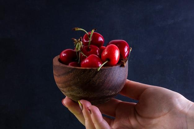 Вид спереди девушка держит в руке вишни в деревянной миске на черном