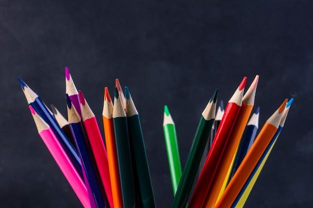 Вид сбоку кучу цветных карандашей на темном