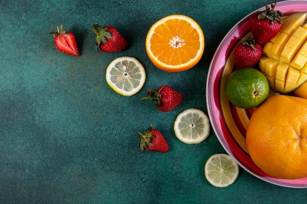 Вид сверху копия пространства фруктовый микс манго клубника лайм и апельсин на зеленый