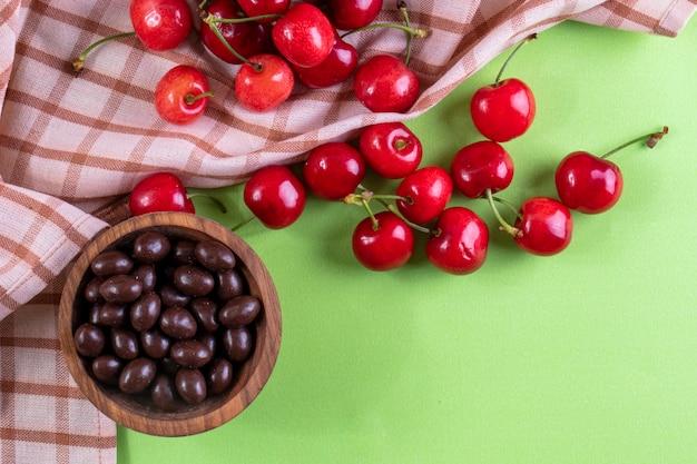 Вид сверху красная вишня с конфетами и кухонное полотенце на светло-зеленом
