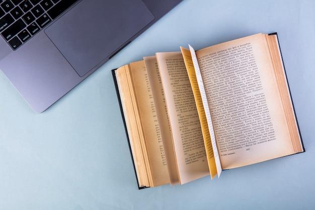 Вид сверху открытой книги и ноутбука на синем