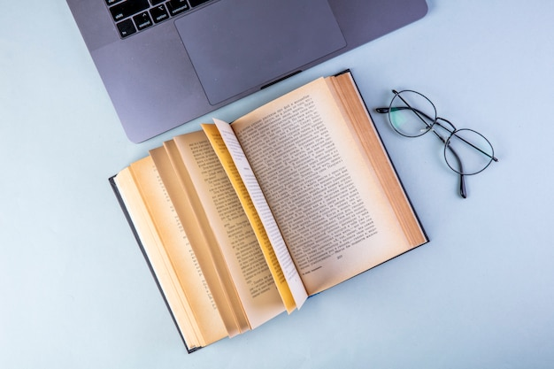 Вид сверху открытой книги с очками и ноутбуком на синем