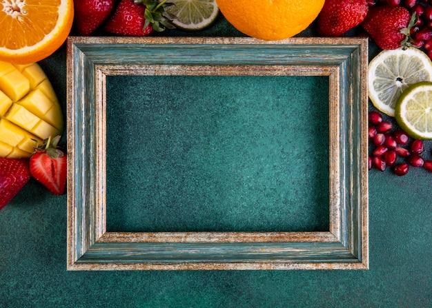 緑のフレームとフルーツマンゴーバナナイチゴレモンオレンジの平面図コピースペースミックス