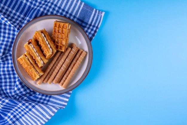 Вид сверху копией пространства сладких булочек с вафлями на тарелке на кухонном полотенце на синем