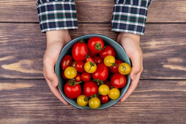 木製のテーブルにトマトのボウルを保持している女性の手の上から見る