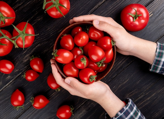 Взгляд сверху рук женщины держа миску томатов с другими на деревянном столе