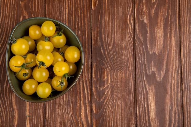 左側と木製のテーブルの上のボウルに黄色のトマトのトップビュー