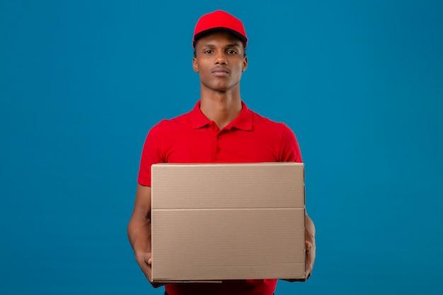 赤いポロシャツと分離された青に深刻な顔をして段ボール箱の地位を保持しているキャップを着ている若いアフリカ系アメリカ人の配達人