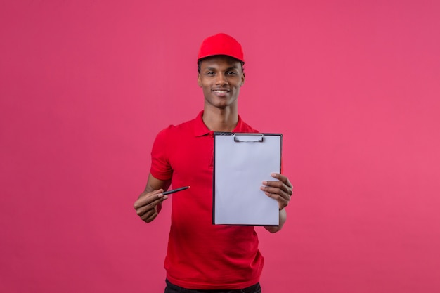 Молодой афроамериканец доставляющий носить красную рубашку поло и шапку, держа буфера обмена, показывая на камеру и указывая пером на нем, улыбаясь на изолированных розовый