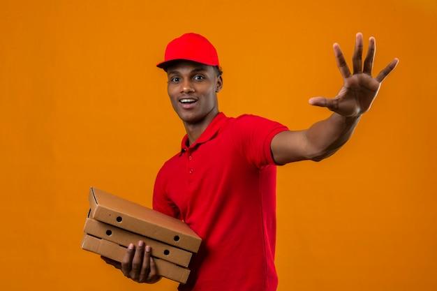 Молодой афро-американский работник доставляющий покупки на дом нося красную рубашку поло и крышку держа пакет салютуя с рукой с счастливым выражением над изолированным апельсином
