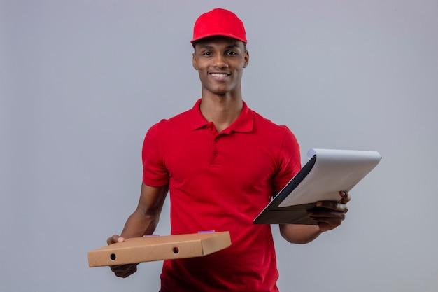 赤いポロシャツと分離の白で顔に笑顔でピザの箱とクリップボードを保持しているキャップを着ている若いアフリカ系アメリカ人の配達人