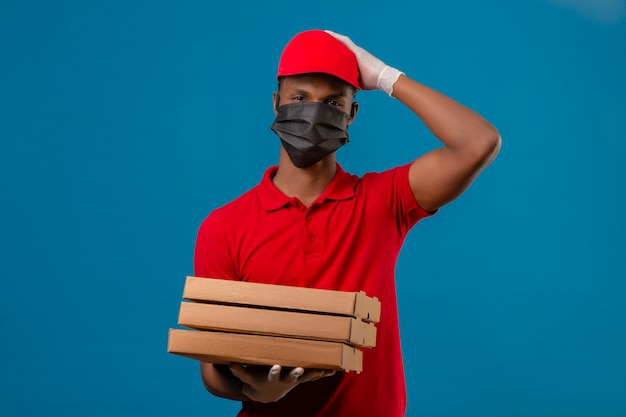 若いアフリカ系アメリカ人の配達人が赤いポロシャツとキャップを身に着けている防護マスクとピザボックスのスタックで立っている手袋を誤った悪い記憶概念の頭の上の手で驚いた