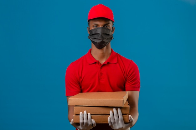 赤いポロシャツと防護マスクと分離の青の上の深刻な顔をしたピザの箱のスタックで立っている手袋でキャップを着ている若いアフリカ系アメリカ人の配達人