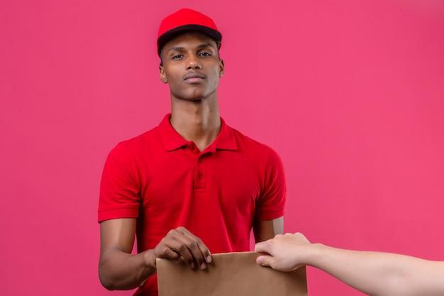 赤いポロシャツとキャップを分離したピンクの上の顧客に自信を持って与える紙箱を探している身に着けている若いアフリカ系アメリカ人の配達人