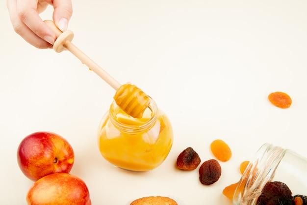 Вид сбоку рукой, держащей стеклянную банку персикового джема с персиками изюм на белой поверхности